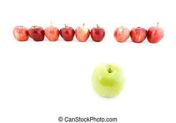 A green apple is different from the rest of the red apples