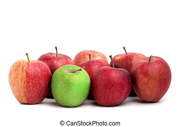 A lone green granny smith apple sits amongst a crowd of red delicious apples.