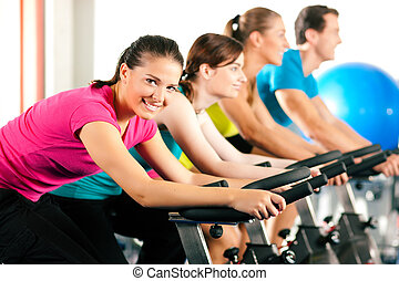 Indoor bycicle cycling in gym - Group of four people...