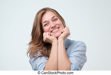 Indoor close up shot of young attractive european woman, smiling warmly and friendly while listening to you