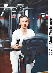 Indoor cycling woman doing cardio workout biking on indoors gym bike.
