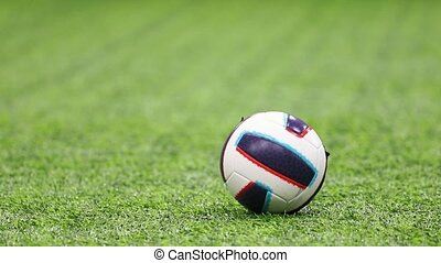 Indoor football arena. A football ball. A kid kicking it....