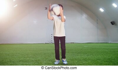 Indoor football arena. A little boy playing with a ball