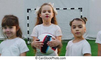 Indoor football arena. Children standing in the line....