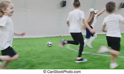 Indoor football arena. Children standing in the line then the game starts and they start running