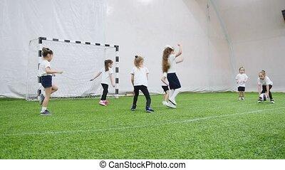 Indoor football arena. Happy little kids playing dodgeball....