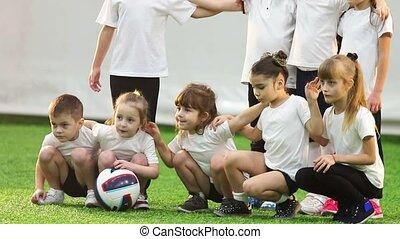Indoor football arena. Kids football team posing for a team...