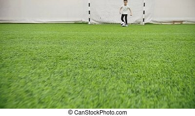Indoor football arena. Little boy leads the ball alone. Mid...