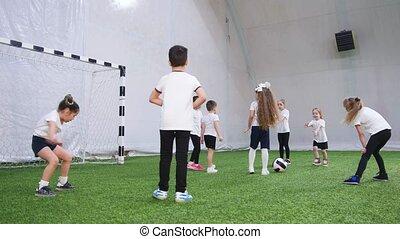Indoor football arena. Little kids playing dodgeball. Back...