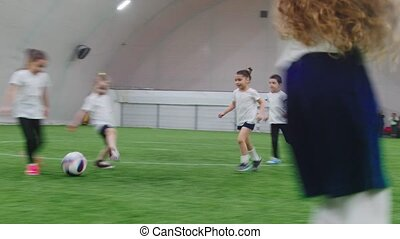 Indoor football arena. Little kids playing football. Mid...