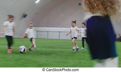 Indoor football arena. Little kids playing football. Mid...