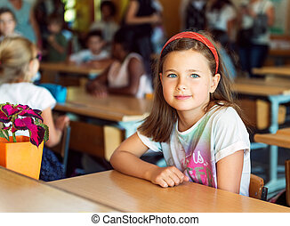Indoor portrait of a cute little girl in a classroom