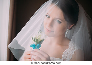 Indoor portrait of sensual, very beautiful bride in veil, holding cute little boutonniere, close-up