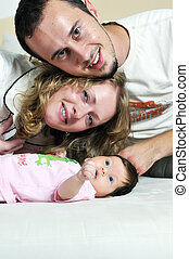 indoor portrait with happy young famil and  cute little babby