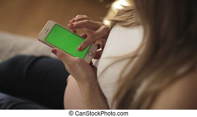 Indoor shot of a woman using smartphone with green screen...