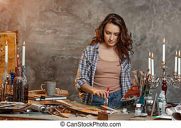Indoor shot of beautiful brunette female painter wearing shirt and jeans, holding paint brush and palette in hands standing near work table, creating sketch, focus into draft while being glad to paint. Drawing supplies, oil paints, artist brushes, canvas, candle, oil lamp. Workshop or art class. Creative concept