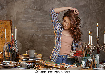 Indoor shot of beautiful brunette female painter wearing shirt and jeans, holding paint palette in hands standing near work table, creating sketch, focus into draft while being glad to paint. Drawing supplies, oil paints, artist brushes, canvas, candle, oil lamp. Workshop or art class. Creative concept