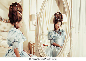 Indoors shot in the Marie Antoinette style. A young sexy girl in a lush blue retro dress with a high hairstyle sitting on the bed and looking in the mirror. Woman tired of luxury