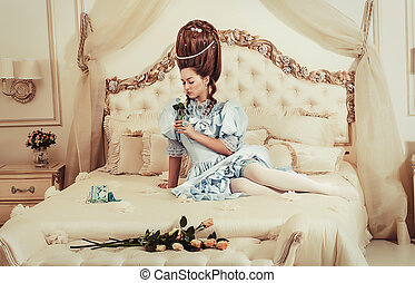 Indoors shot in the Marie Antoinette style. A young sexy girl in a lush blue retro dress with a high hairstyle lies on the bed with a flower in her hand. Woman tired of luxury