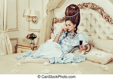 Indoors shot in the Marie Antoinette style. A young sexy girl in a lush blue retro dress with a high hairstyle lies on the bed with a glass of sparkling wine in her hand. Woman tired of luxury