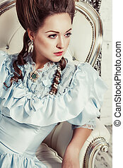 Indoors shot in the Marie Antoinette style. A young sexy girl in a lush blue retro dress with a high hairstyle sits on sofa. Woman tired of luxury