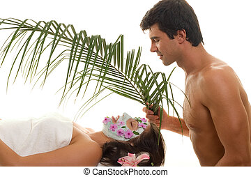 A young woman is gently fanned with a palm frond at a day spa or exotic beauty salon or perhaps she is pampered by her husband or lover