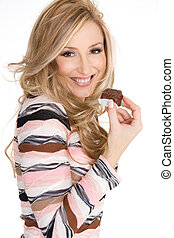 Fun-loving smiling female holding a delicious milk chocolate truffle