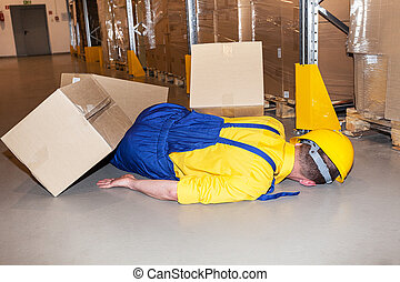 Industrial accident - Worker in hard hat hit by cardboard in...