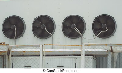Industrial air conditioning system. Large fans on wall of the building