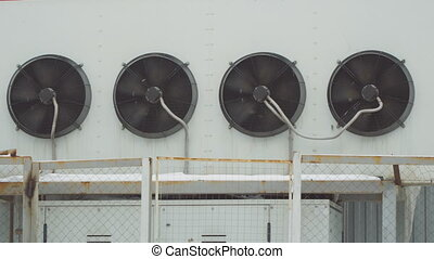 Industrial air conditioning system. Large fans on wall of...