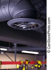 Black industrial air duct and vent or register hanging from an unfinished ceiling in a commercial space under construction