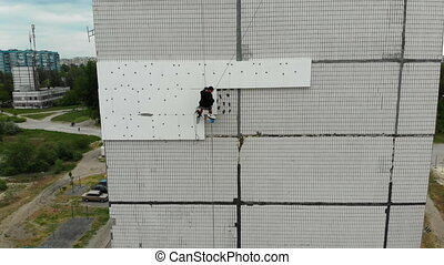 Aerial View on Industrial Climber Suspended on Ropes Performs Work on Insulation Facade of High-rise Building using Styrofoam. Industrial alpinism. Drone view on side multi-story residential building