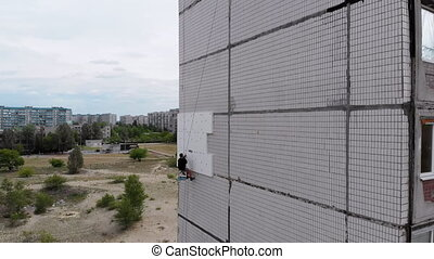 Industrial Alpinism. Aerial View work on the outer Insulate of an apartment house using Styrofoam. The Drone View on climber suspended on ropes performs work on warms of a facade high-rise building.
