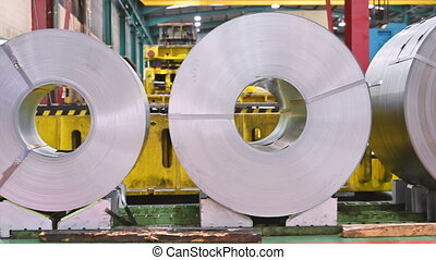 Industrial background. Big size steel coil stored inside industrial warehouse .
