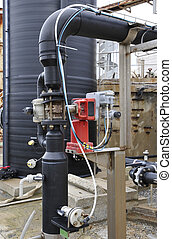 Industrial black plastic tank and control system with some branchs and pumps