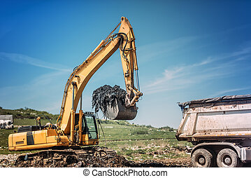 Industrial bulldozer and excavator working on site.