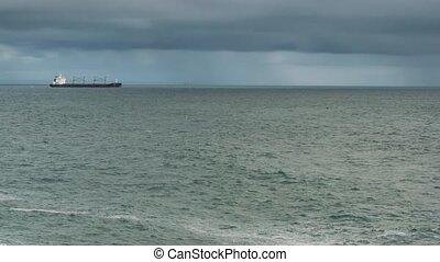Industrial cargo tanker ship in blue ocean waters transporting loads to destination in the calm waters of Atlantic ocean - timelapse.