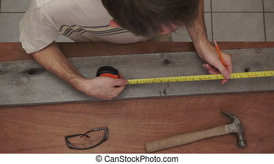 Industrial Carpenter Measuring Wood - Overhead shot of a...