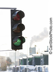 industrial chimney and green traffic light