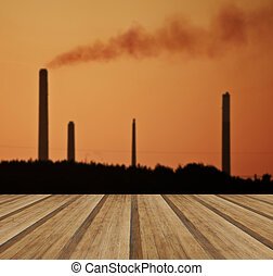 Industrial chimney stacks in natural landscape with wooden plank