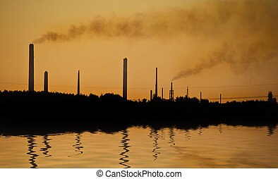 Industrial chimney stacks polluting the air in a natural landscape setting