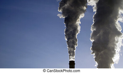 industrial chimneys emits toxic pollutants into the sky polluting the environment.