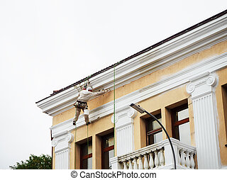 Industrial climber hanging from the roof paints the cornice of the building