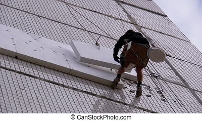 Industrial Climber Suspended on Ropes Performs Work on Insulation of the Facade of High-rise Building using Styrofoam. Slow Motion 180 fps. Warms old panel multi-story building using Foam. Bottom view