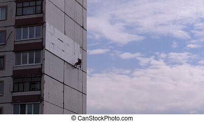 Industrial Climber Suspended on Ropes Performs Work on the Insulation of the Facade of High-rise Building using Styrofoam. Warms an old panel multi-story residential building using Foam. Bottom view