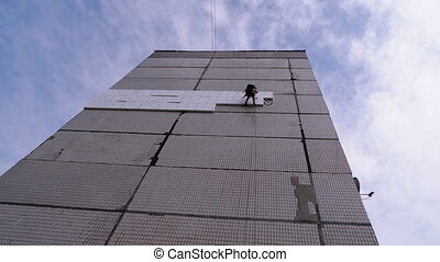 Industrial Climber Suspended on Ropes Performs Work on the Insulation of the Facade of Building with Styrofoam. Warms an old panel high-rise multi-story residential building using Foam. Bottom view