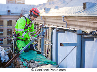 Industrial climber on roof of a building - Industrial...
