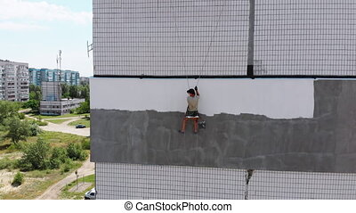 Aerial View on Industrial Climber is Painting a Building Wall after Insulation Work of Facade of Apartment Building. Foam insulation, Warming. High-altitude work on the ropes. Drone Side view.