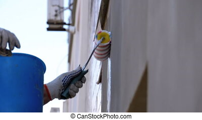 Industrial Climber Primers the Wall of Building with a ...
