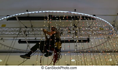 Industrial climber sets up Christmas decorations in the...